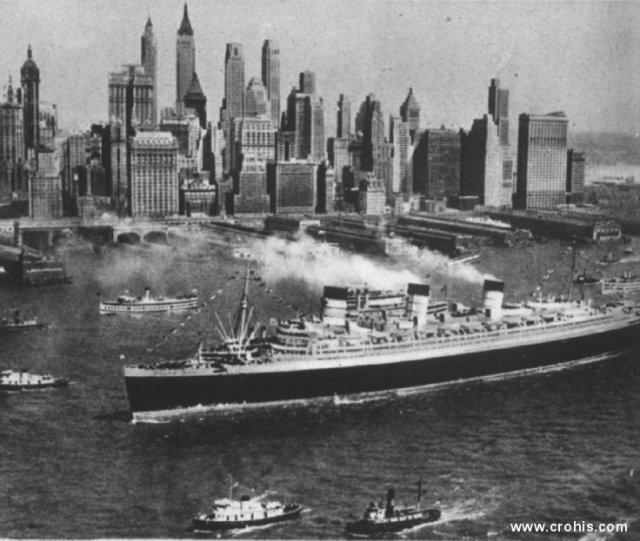 """Manhattan gledan s mora. emelj uspona New Yorka je, kao i slučaju Londona, njegova luka. U razdoblju između dva svjetska rata brzina prijelaza oceana velikim prekooceanskim brodovima, kao ovim na slici, bila je stvar nacionalnog prestiža. Iz toga se razvilo natjecanje za """"plavu vrpcu"""" koju je dobivao brod koji je najbrže plovio s jedne na drugu stranu Atlantika."""