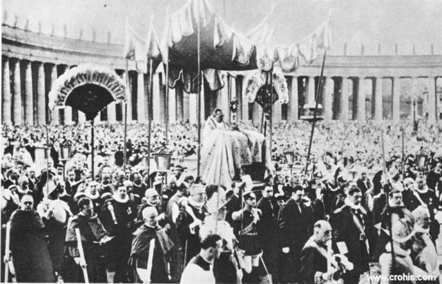 Tijelovska procesija u Rimu. Uz nova, velika i moderna okupljanja 30-tih godina 20. st. pozornost privlače i ona drevna, tradicijska, vjerska. O ovome svjedoči i mnoštvo na Trgu Sv. Petra tijekom tijelovske procesije. Slika je osobito važna jer prikazuje samog Svetog Oca, papu da predvodi obred. To se dogodilo prvi put poslije 1870. kada je talijanska vojska zauzela Rim, a papa se proglasio zatočenikom Vatikana. Odraz je poboljšanja odnosa između Svete stolice i talijanske države poslije sklapanja Vatikanskih ugovora 1929.